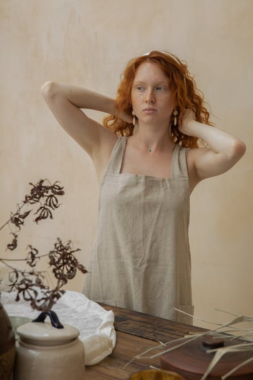Craftswoman touching red hair at table in workshop