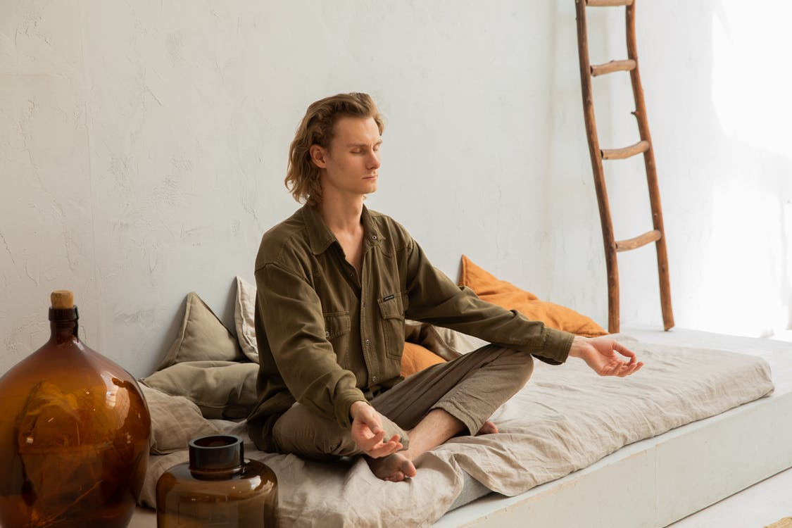 Young mindful barefoot male with closed eyes sitting in Padmasana pose while practicing yoga at home
