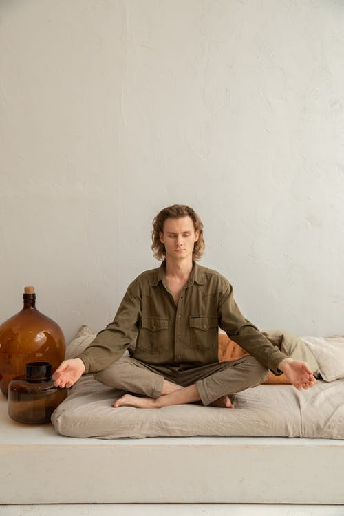 Young reflective barefoot male sitting in Padmasana pose with closed eyes on cozy mattress in house