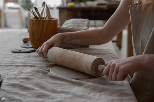 Crop craftswoman rolling out clay mass in workroom