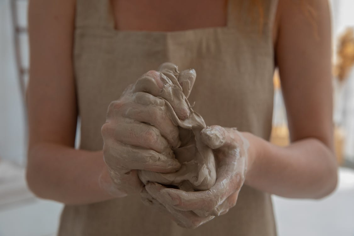 Crop faceless woman kneading clay in workshop