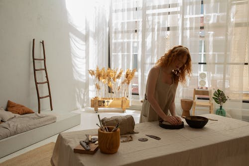 Concentrated redhead female wearing light apron kneading clay in baking pan while creating in modern apartment