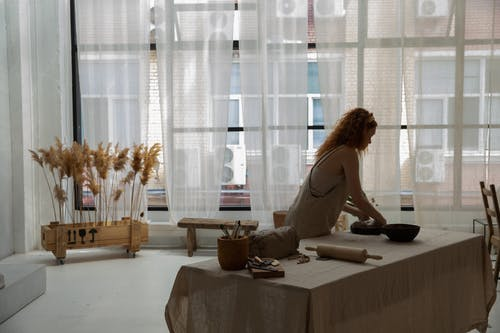Side view faceless female wearing apron placing clay slab on baking pan while making earthenware in contemporary studio