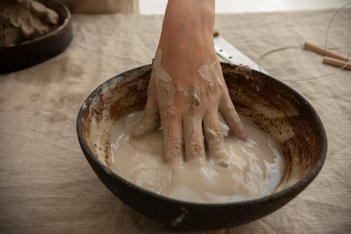 Crop ceramist with hand in clay