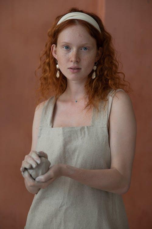 Спокойная рыжая женщина с глиной