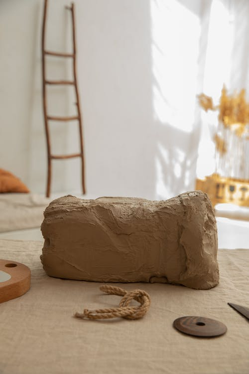 Chunk of natural clay placed on workbench with textile in light room with wooden ladder and plants on blurred background