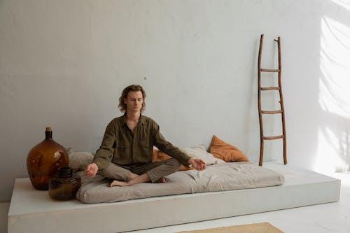 Vreedzame Man Mediteren Op Bed In Lotus Houding
