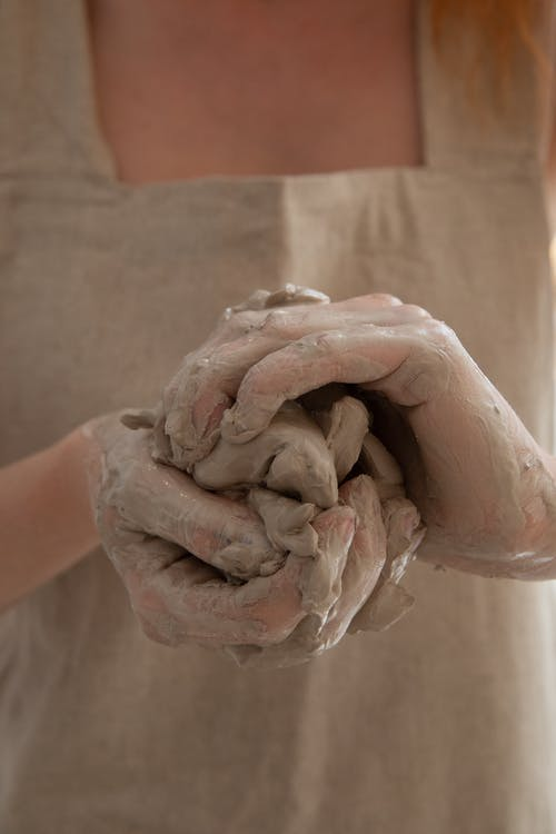 Unrecognizable person wearing gray apron shaping and molding clay in dirty hands while making handicraft crockery in workshop during work