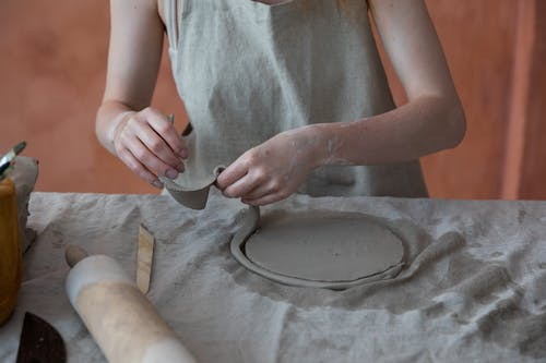 Unrecognizable skilled female master in apron standing near table with rolling pin and working with clay while making crockery during work in pottery workshop with blurred background