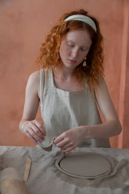 Redhead woman working with clay