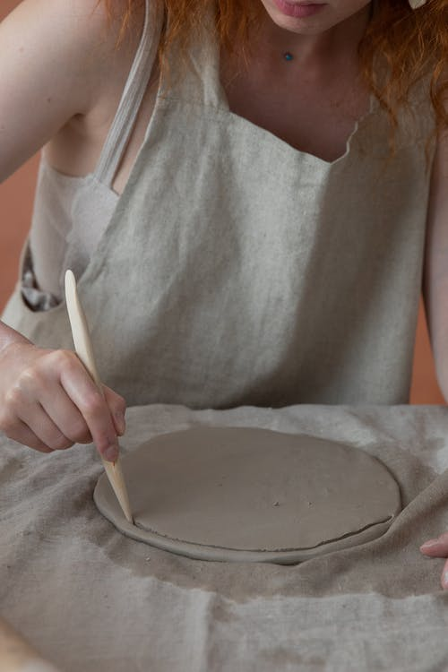 Unrecognizable female master in apron cutting round piece of clay with knife while making pottery during work in professional studio