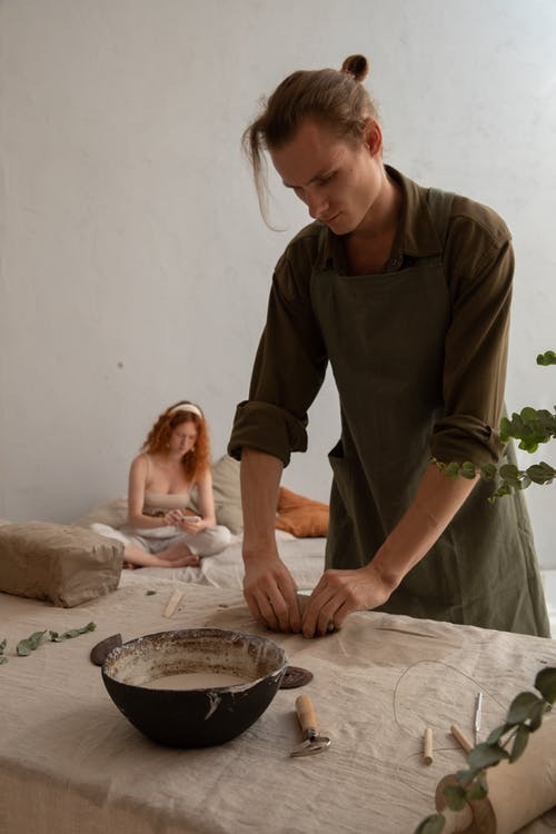 Professional male potter standing at workbench and shaping piece clay while working in studio with redhead woman sitting on background
