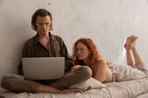 Focused couple browsing laptop on bed