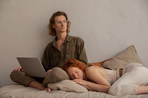 棕色按鈕襯衫坐在床上使用macbook的女人