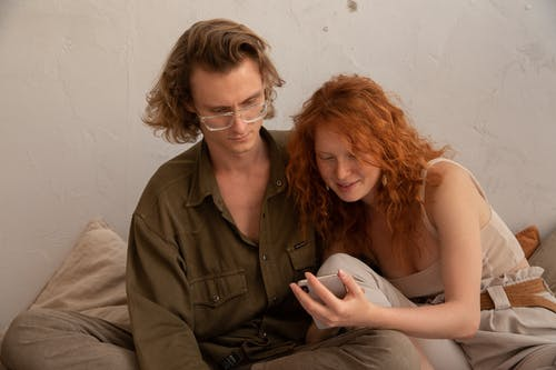Calm couple in casual clothes browsing smartphone and looking at screen while resting together in light room in apartment