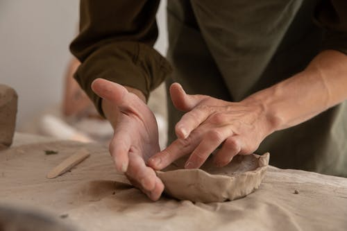 Crop unrecognizable male artisan in casual clothes sculpting from clay while working in creative studio in daytime