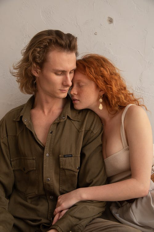 Romantic couple in casual clothes hugging with closed eyes while resting together at home against light wall