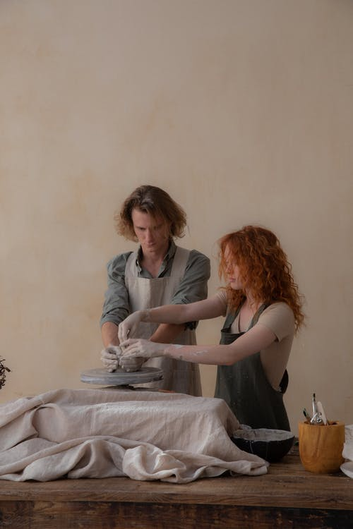 Concentrated young couple in aprons standing at table and creating clay vase in workshop