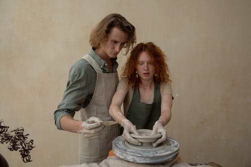 Focused couple in aprons with dirty hands modelling clay products on wheel while working together at home