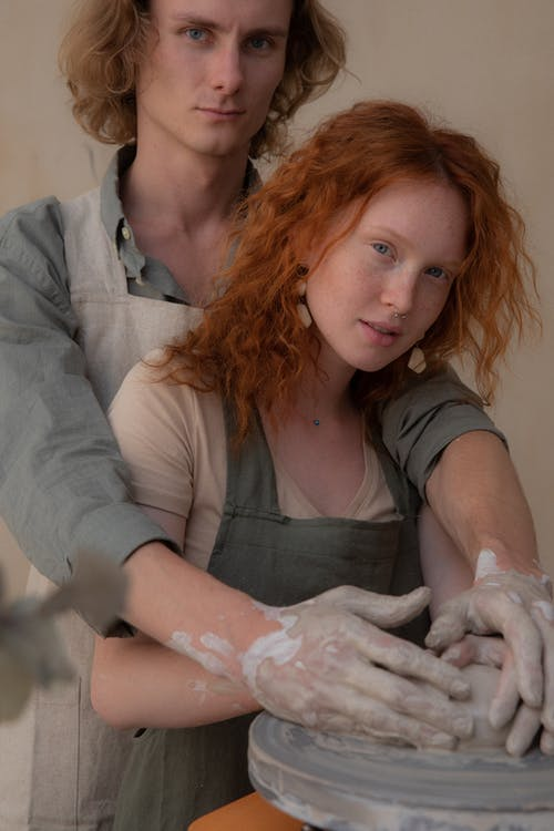 Crop young couple in aprons hugging while modelling clay products together and looking at camera