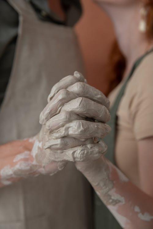 Crop couple holding hands in argilla