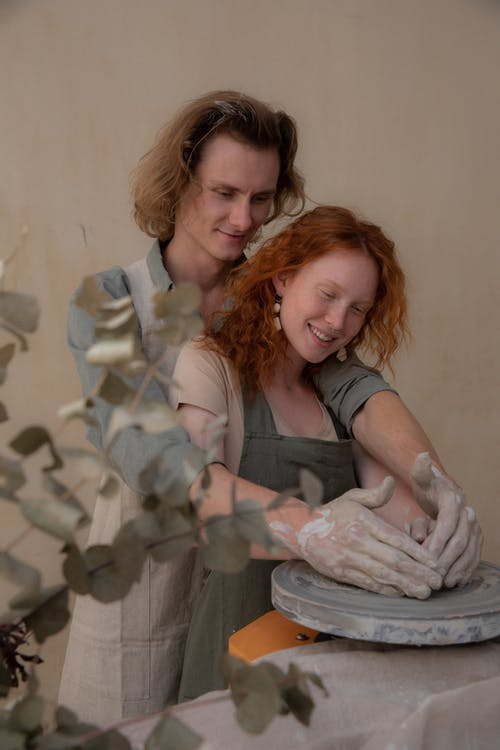 Smiling couple with dirty hands embracing while modelling clay products together at home