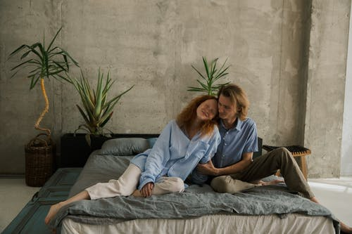 Full body of cheerful couple cuddling while sitting on bed in room with shabby wall and green plants during weekend together