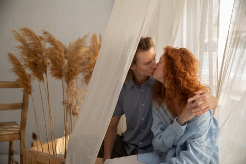 Redhead girlfriend and boyfriend kissing and holding hands while sitting near window with white curtain in room with dry plants