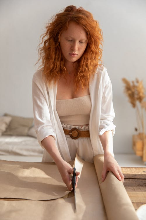 Focused female with red hair cutting craft paper with scissors while standing near wooden table in workshop on blurred background