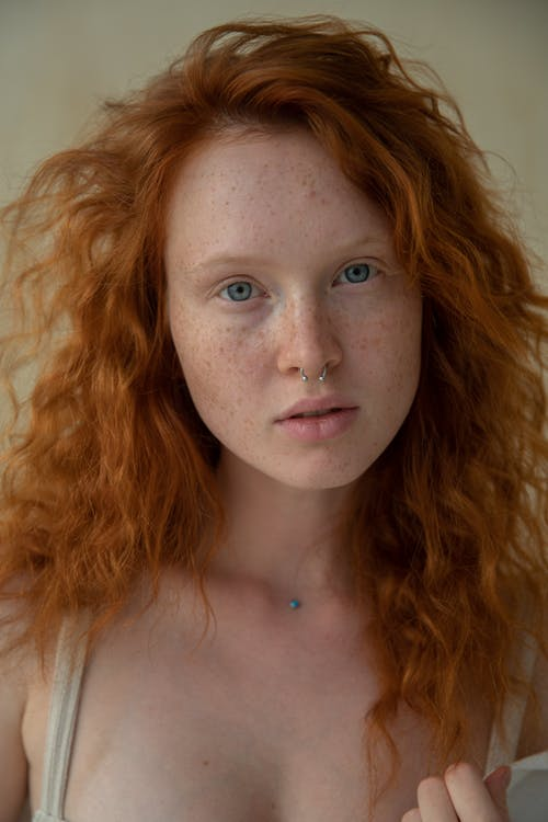 Portrait of dreamy female with curly red hair and freckles with pierced nose looking at camera while standing on background