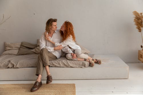 Full body of romantic couple hugging and looking at each other while sitting on comfortable mattress near wall in cozy room