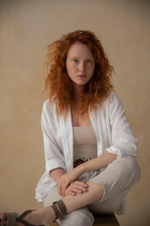 Stylish redhead woman against wall