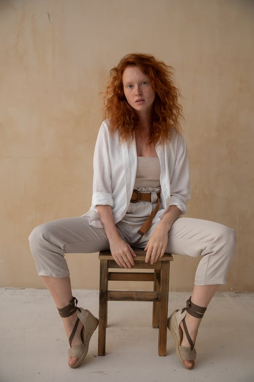 Full body of elegant female with red hair sitting on chair against wall with legs spread and looking at camera