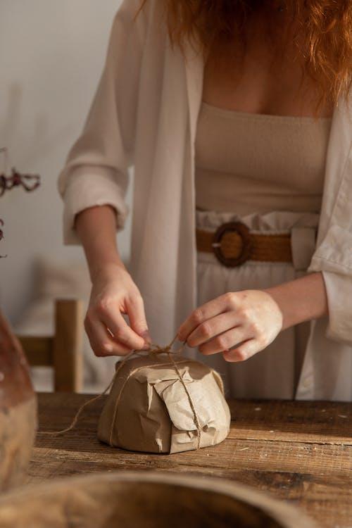 Crop craftswoman tying threads on plate
