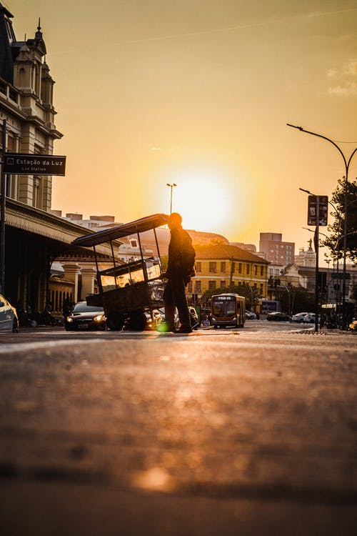 Silhouette of unrecognizable man with selling cart crossing street with traffic at sundown