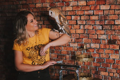 Woman in Yellow and Black Crew Neck T-shirt Holding Brown and White Owl