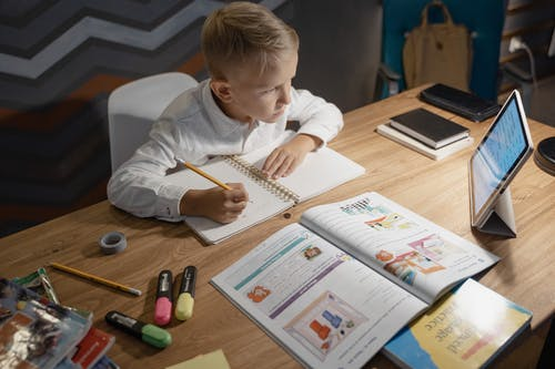 Boy in White Long Sleeve Shirt Writing on White Paper