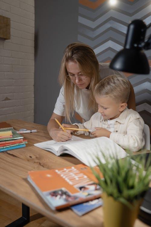 Бесплатное стоковое фото с aan lichtbak toevoegen, menino lendo um livro, o menino escreve em um caderno