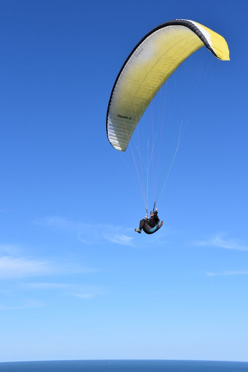 Person in Yellow Parachute Under Blue Sky