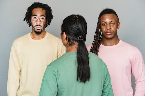 Multiethnic men standing against gray background
