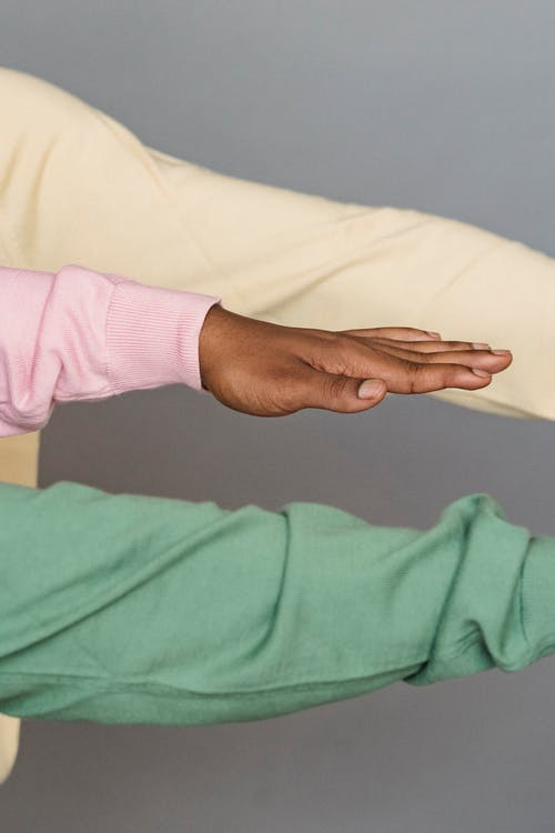 Crop faceless ethnic people in pullovers with trendy colors showing hands against gray background
