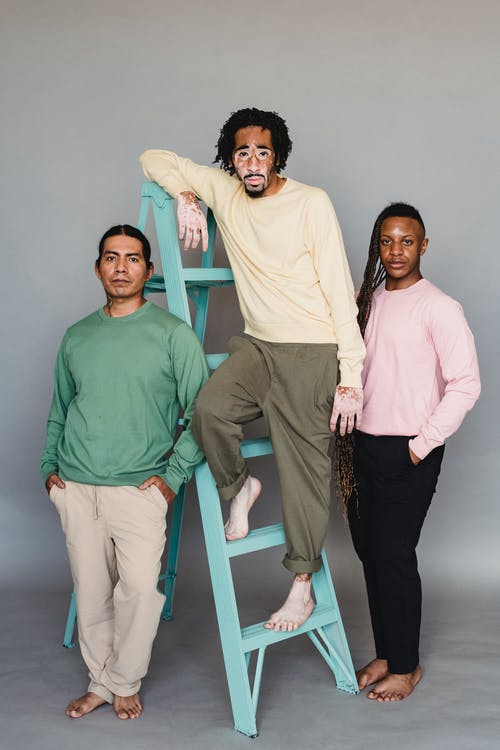 Full body of multiracial barefoot male models in casual clothes standing near ladder against gray background and looking at camera