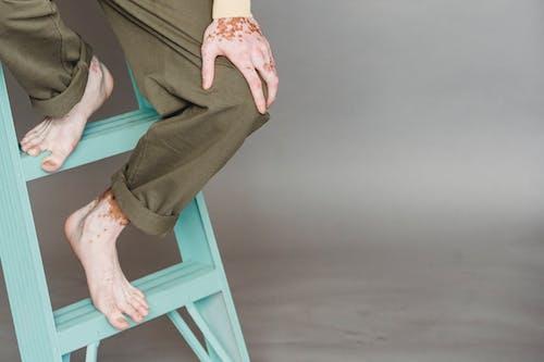 Crop man sitting on ladder in modern studio