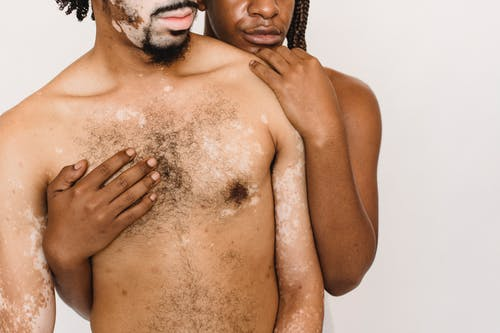 Crop faceless African American couple with naked torso standing close and hugging against white background