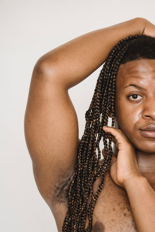 African American transgender with naked torso touching Afro braids and looking at camera while standing with hand on head on white background