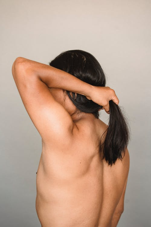 Back view anonymous nude male with long black hair doing ponytail while standing against gray background in studio