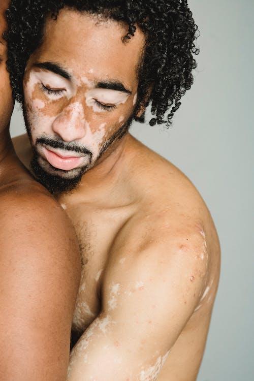 Crop shirtless man with eyes closed embracing boyfriend