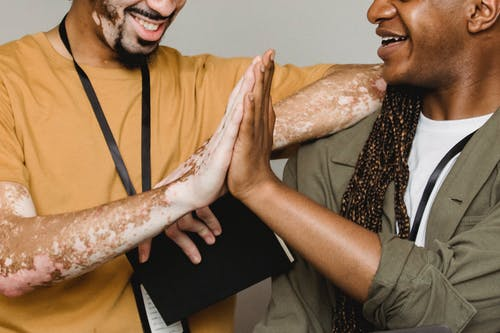 Crop smiling African American male with vitiligo skin giving high five to colleague in studio