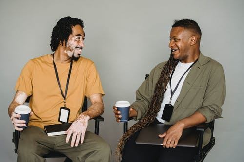 Smiling African American male in casual wear with vitiligo skin sitting on chair and talking to androgynous male coworker with laptop during coffee break
