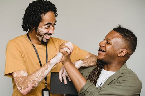 Laughing black male colleagues clasping hands in excitement together